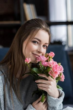 happy girl hugging bouquet of pink roses and looking at camera, 8 march concept