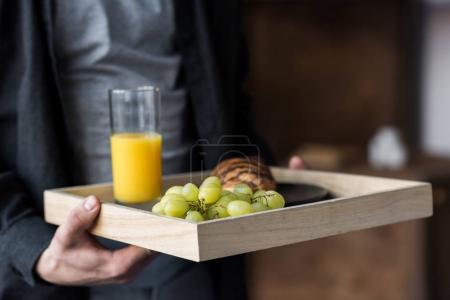 cropped image of man holding tray with breakfast