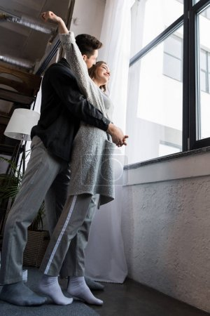 bottom view of boyfriend hugging girlfriend near window in morning