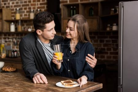 boyfriend hugging girlfriend with orange juice