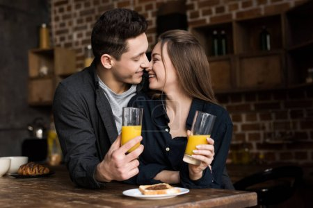 smiling couple with orange juice going to kiss at kitchen