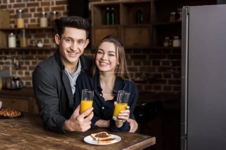 Photo pour Couple souriant avec du jus d'orange regardant la caméra - image libre de droit
