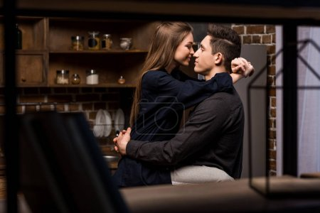girlfriend sitting on table in kitchen and going to kiss boyfriend