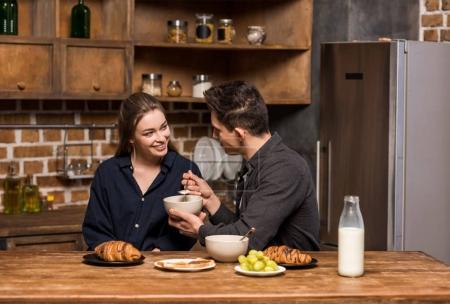 boyfriend asking girlfriend to taste breakfast in kitchen