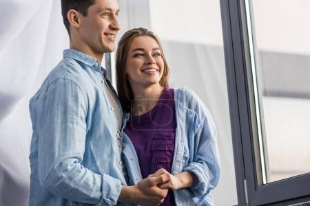 happy couple holding hands and looking away