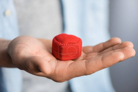 cropped image man holding red box with engagement ring on palm