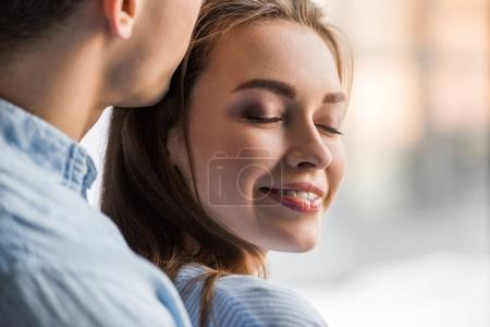 cropped image of boyfriend kissing happy girlfriend