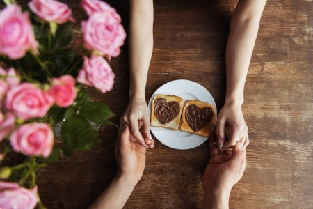 cropped image of couple holding hands near toasts with chocolate paste in shape of hearts, valentines day concept