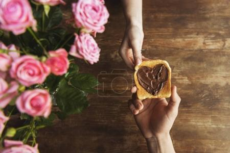 cropped image of couple holding toast with chocolate paste in shape of heart, valentines day concept