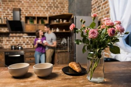 couple with coffee in kitchen, plates and bouquet on foreground