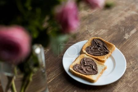 toasts with chocolate paste in shape of hearts on wooden table, valentines day concept