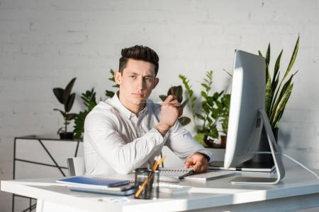 serious thoughtful businessman sitting at workplace and looking away