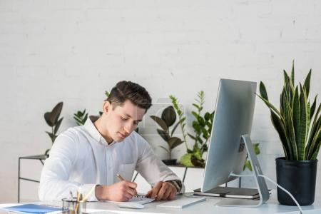 Concentrated young businessman making notes at wor...
