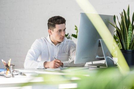 Photo pour Beau jeune homme d'affaires écrivant des notes sur le lieu de travail - image libre de droit