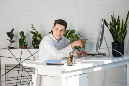 Photo pour Heureux homme d'affaires jeune pointant sur écran d'ordinateur - image libre de droit