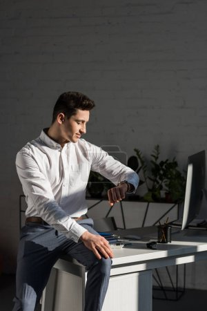 handsome young businessman sitting on work desk and looking at watch