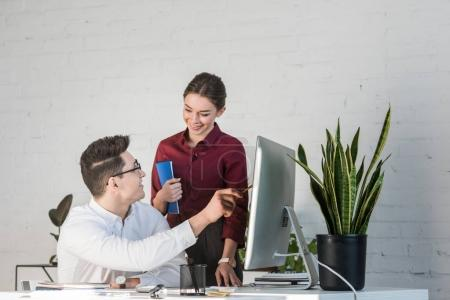 young managers working with computer together at workplace in modern office
