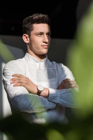 handsome young businessman with crossed arms looking away