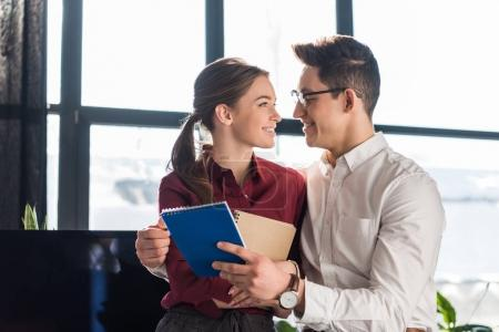 attractive young managers couple embracing at office, workplace romance concept