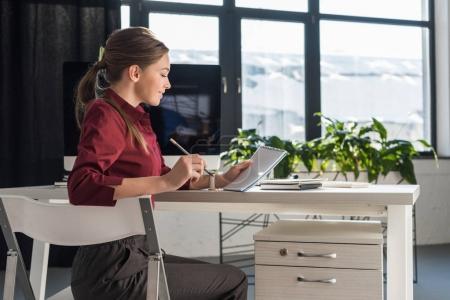 Photo pour Belle jeune femme d'affaires prenant des notes au travail - image libre de droit