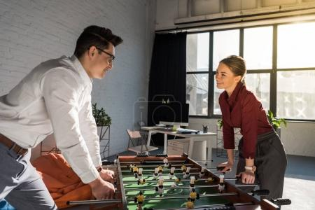 young business partners playing table football at modern office