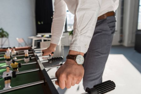 cropped shot of businessman playing table football at office