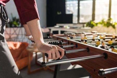cropped shot of businesswoman playing table football at office