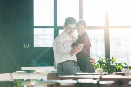 young businesspeople couple at modern office using smartphone together