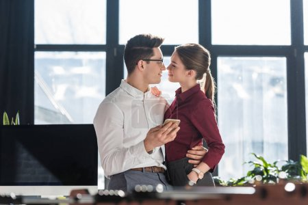 attractive kissing young businesspeople in formal clothing having office romance