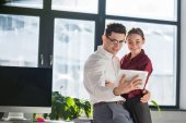 flirting colleagues embracing and using smartphone together at office