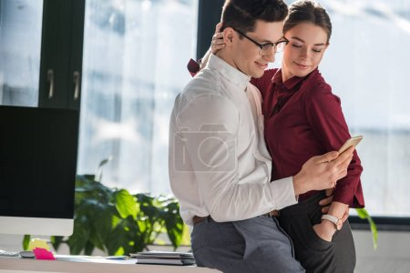 colleagues embracing and using smartphone together at office
