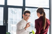 young businessman showing okay sign to his colleague