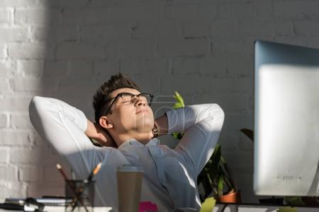 handsome young businessman relaxing at workplace in modern office