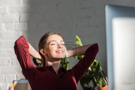 Photo pour Heureuse jeune femme d'affaires se détendre sur le lieu de travail - image libre de droit