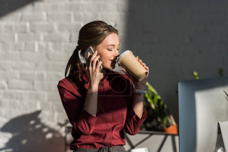 beautiful young businesswoman drinking coffee from paper cup and talking by phone at office
