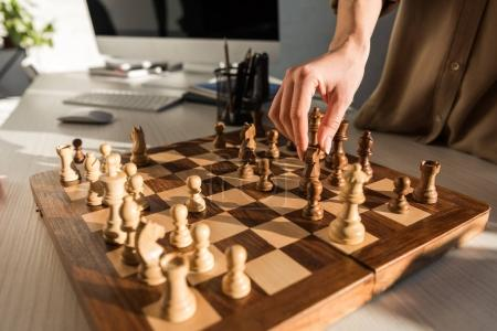 cropped shot of woman making move while playing chess at workplace