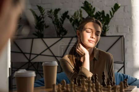 young beautiful woman playing chess while sun shining at her face