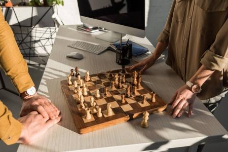 cropped shot of colleagues playing chess at workplace