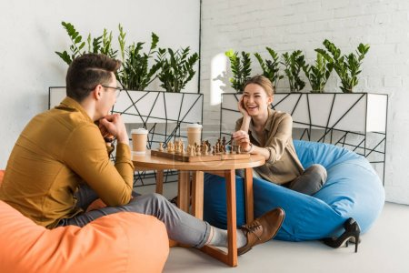 young happy friends playing chess while sitting on beanbags