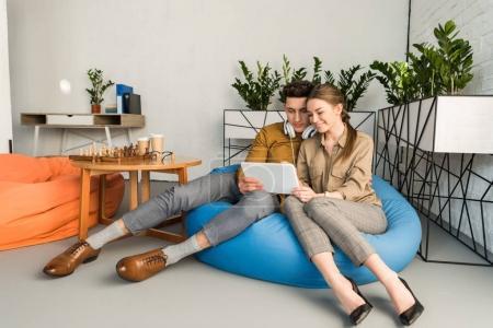 Photo pour Heureux jeune couple en utilisant la tablette ensemble tout en étant assis dans un sac de haricots - image libre de droit