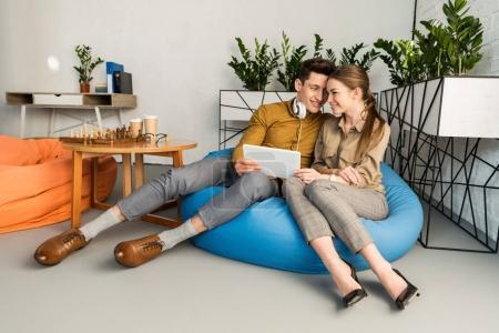 Photo pour Jeune couple câlin en utilisant la tablette ensemble tout en étant assis dans un sac de haricots - image libre de droit