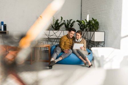 happy young couple using tablet together while sitting in bean bag