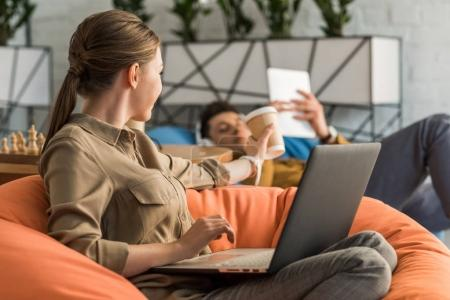 young woman drinking coffee and working with laptop while sitting in bean bag and passing cup to boyfriend