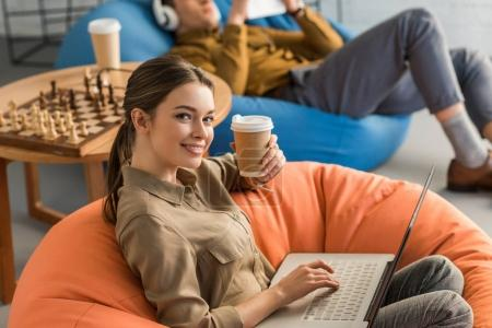 happy young woman drinking coffee and working with laptop while sitting in bean bag