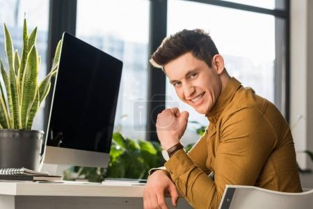 happy young businessman celebrating success at workplace and looking at camera
