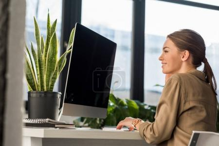 smiling young manageress working with computer