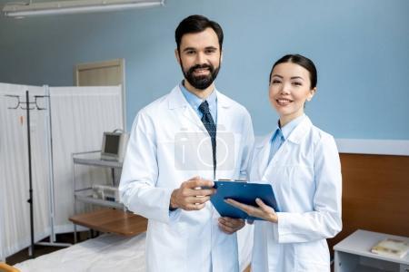 Foto de Dos médicos que diagnóstico y posando en la sala de hospital - Imagen libre de derechos