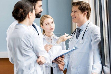 Photo pour Vue latérale de l'équipe de médecins discutant du diagnostic à l'hôpital, concept de médecins soignants - image libre de droit