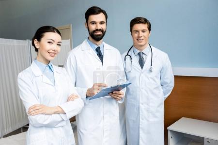Foto de Tres doctores que diagnóstico y posando en la sala de hospital - Imagen libre de derechos