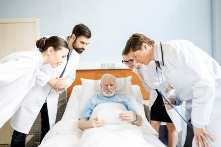 Photo for Professional young doctors looking at senior patient using digital tablet in hospital bed, elderly patient with doctors concept - Royalty Free Image